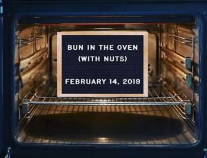 Sign reading 'bun in the oven' is in the oven for pregnancy announcement