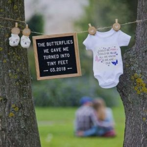 Pinned baby items and pregnancy announcement sign
