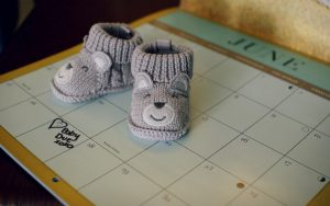 Tiny baby shoes on calendar used for pregnancy announcement