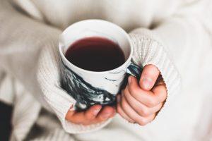 cup of tea held in womans hands