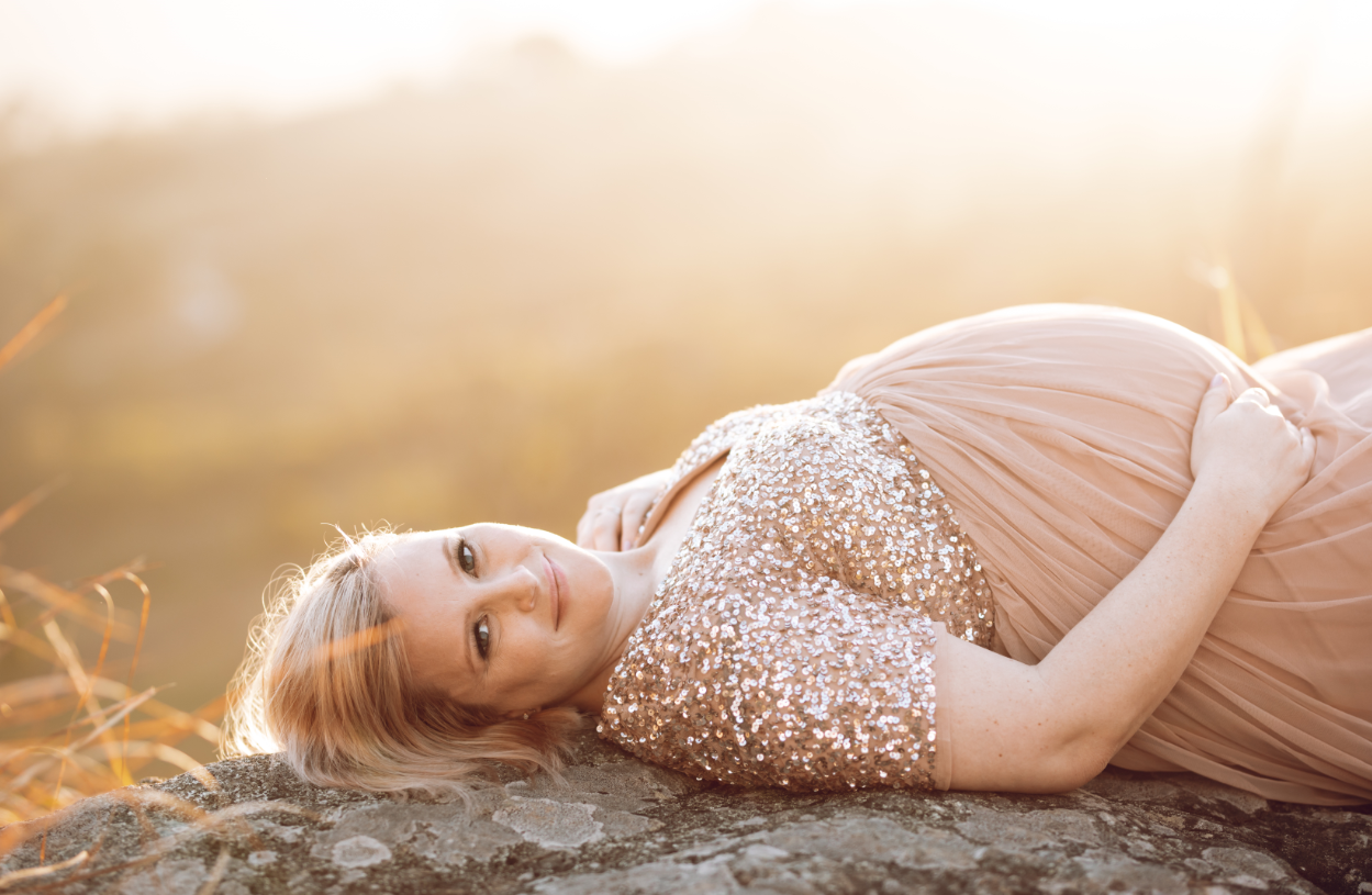Pregnant Charmaine from The Bump Box Co. during a maternity shoot, laying on a rock in the sunset