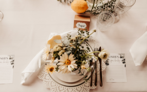 table settings at a baby shower, flowers in watering cans on lace doilies