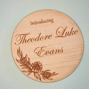 """wooden baby name announcement disc reading """"introducing Theodore Luke Evans"""" with a king protea embellishment"""