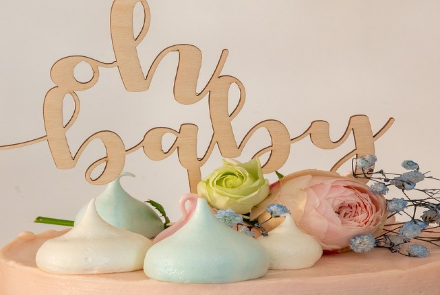 """A cake topper from a baby shower that reads """"oh baby"""""""