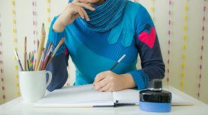 woman's torso at table with pencils and paper apparently thinking