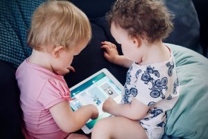 two babies playing on a tablet computer