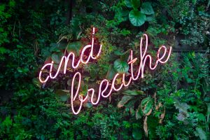 neon sign reads 'and breathe' in amongst greeney