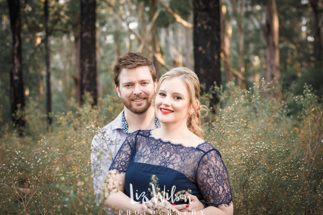 couple standing in amongst forest smiling